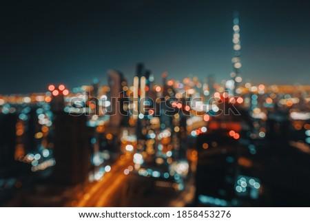 Blur Nighttime Cityscape. Abstract Background of an Urban Night Scene. Bokeh Lights. Modern City of Dubai. United Arab Emirates. Royalty-Free Stock Photo #1858453276