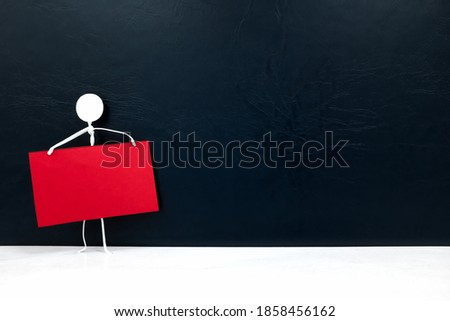 One stick man figure holding blank red placard or notice or announcement board in black background. Activism, protest, demonstration, social movement and freedom of expression template concept.