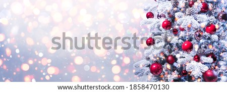Abstract Holiday Background - Snowy Christmas Tree With Red Baubles With Shiny Defocused Lights #1858470130