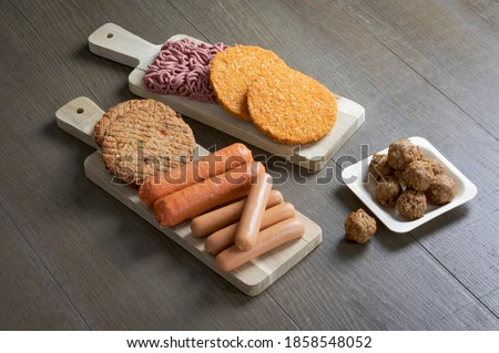 Display of plant based vegetarian meat products for a plant based diet on a wooden table Royalty-Free Stock Photo #1858548052