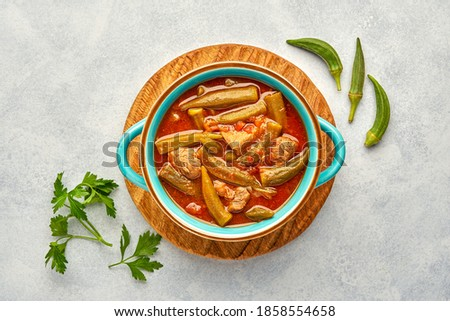 Homemade okra and meat stew in a pot. Top view, copy space