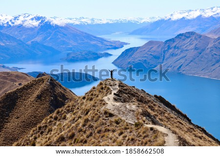Woman standing with arms wide open at the top of the mountain watching a beautiful scenery all alone. Roy's Peak in New Zealand. Lake, snow mountains and blue sky in the background. Royalty-Free Stock Photo #1858662508