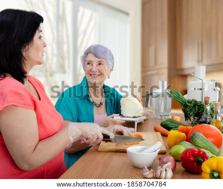 Female caregiver or volunteer and senior adult woman cook vegetable salad together. The old lady looks happy.  Royalty-Free Stock Photo #1858704784