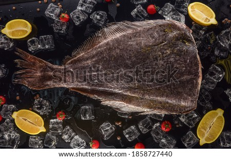 headless halibut with ice, lemon and tomatoes on black background