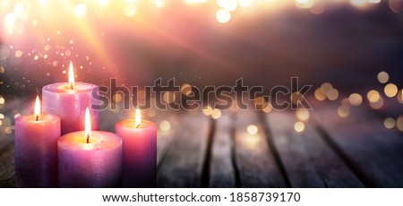 Abstract Advent - Four Purple Candles With Soft Blurry Lights And Glittering On Flames Royalty-Free Stock Photo #1858739170
