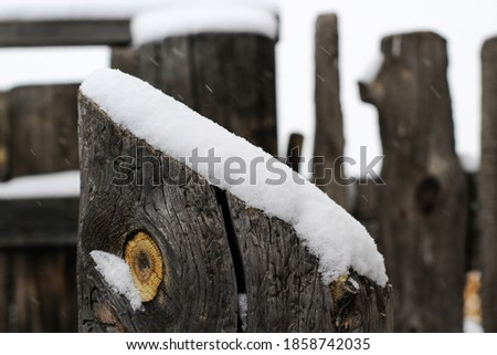 Snowcapped wooden fence in snowy weather and snowflakes falling. White fluffy cold snow in winter