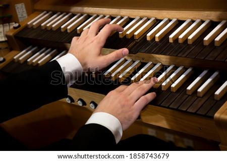 Close up view of a organist hands playing a pipe organ Royalty-Free Stock Photo #1858743679