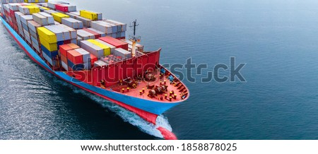 Aerial side view head of cargo ship carrying container and running  near international sea port for export. Royalty-Free Stock Photo #1858878025