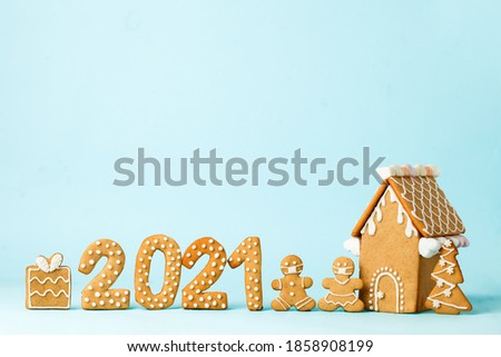 Happy New Year's set of numbers 2021, gingerbread man in face mask, house from ginger biscuits glazed sugar icing decoration on blue background, minimal seasonal pandemic winter holiday card