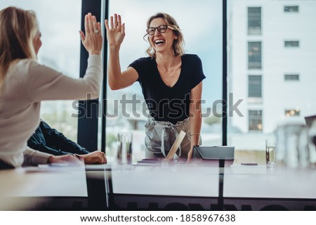 Businesswoman giving high five to colleague in meeting. Happy business professionals having meeting in office conference room. Royalty-Free Stock Photo #1858967638