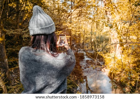 Woman in the fall season sitting on a fence in a forest with orange and yellow tree leaves taking pictures with her smartphone to a river waterfall. The woman is wearing warm clothes