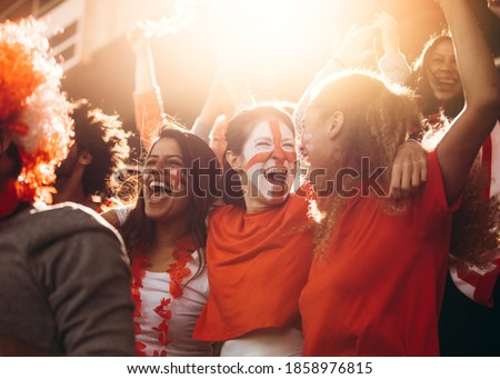 English soccer fans watching the match from the stadium and celebrating after their team scoring a goal. Spectator at stadium cheering when their national team scores a goal. Royalty-Free Stock Photo #1858976815