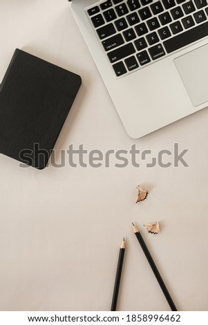 Minimal flat lay, top view lifestyle composition with laptop, pencils, notebook on neutral pastel beige background. Minimal home business workspace. Blog, website, social media concept.