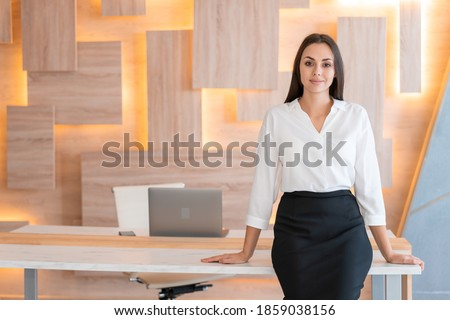 Woman standing near table in wooden office interior room, wearing white shirt and black skirt. Female secretary looking at the camera, smiling. Concept of office worker Royalty-Free Stock Photo #1859038156