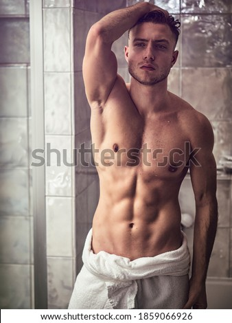 Shirtless muscular handsome man looking at himself in bathroom mirror in the morning after shower or bath, with towel around his waist Royalty-Free Stock Photo #1859066926