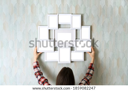 Blank empty frame for multiple photos in female hands, as mockup for your design. Girl holding blank photo frame against wall.