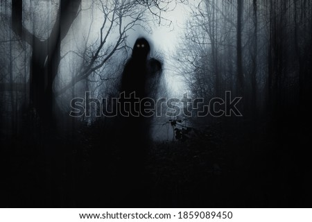 A scary hooded figure with glowing eyes in a spooky forest on a foggy winters day. With a artistic, blurred, abstract, grunge edit. Royalty-Free Stock Photo #1859089450