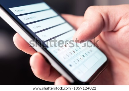 Online form to register personal info and data to web site with mobile phone. Person typing information to internet document, survey or questionnaire with smartphone. Customer registration to website. Royalty-Free Stock Photo #1859124022
