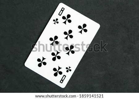 Eight of Clubs playing card, black background.