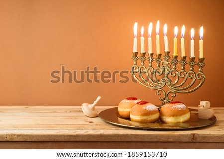 Jewish holiday Hanukkah concept with vintage menorah, candles and traditional donuts on wooden table