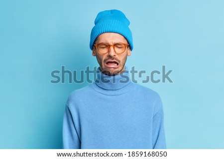 Depressed crying man being in stressful situation stands desperate as faces problem feels regret blames himself in failure wears trendy blue hat turtleneck spectacles poses indoor. Pessimistic person