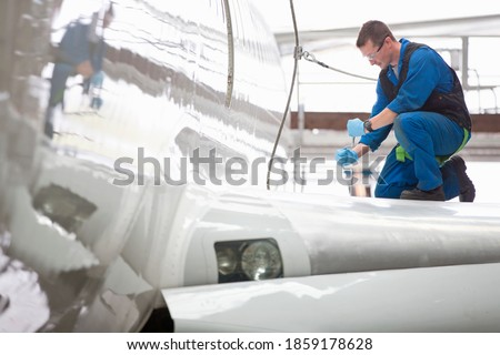 Wide shot of an engineer repairing the wing of a passenger jet at a hangar. Royalty-Free Stock Photo #1859178628