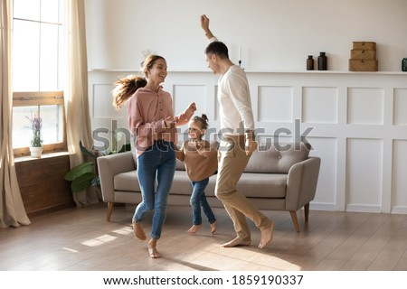 Cheery couple dancing with little daughter barefoot on wooden laminate floor with underfloor heating system in modern warm living room. New home, bank loan and lending, hobby and fun with kids concept Royalty-Free Stock Photo #1859190337