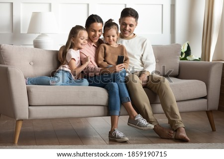 Married couple with 2 preschool adorable daughters resting seated on couch in living room with modern gadget having fun using smartphone. Take family picture, make videocall, parental control concept