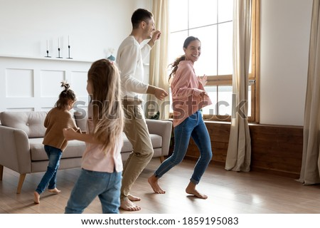 Vivacious family with 2 little daughters play together in cozy living room, people listen funky music dance run barefoot on warm floor at modern own apartment. Happy homeowners enjoy playtime concept Royalty-Free Stock Photo #1859195083