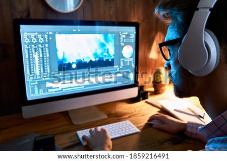 Videographer editor film maker wears headphones using digital software on desktop computer editing video footage content working using post production multimedia making montage, over shoulder view.