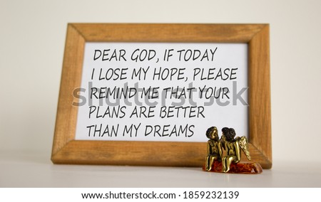Wooden picture frame with Inspirational quote - 'Dear God, if today i lose my hope, please remind me that Your Plans are better than my dreams' on beautiful white fon. Two bronze angeles on the table.