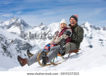 An enthusiastic senior couple riding a sled together while sledding down the slope on a snowy mountain with motion blur