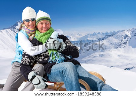 A portrait of a romantic senior couple sitting on a sled while embracing each other at the top of a snowy mountain
