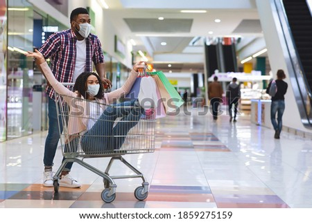 Cheerful black couple in medical face masks having fun while shopping in mall, making purchases during coronavirus pandemic, playful man pushing trolley with his girlfriend inside, copy space Royalty-Free Stock Photo #1859275159