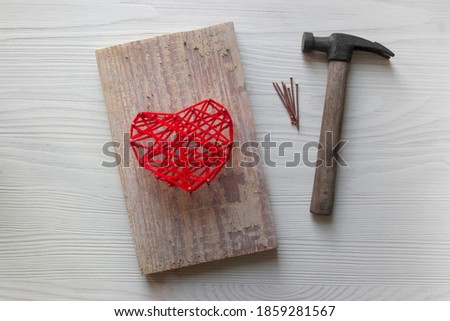 Step by step instruction: DIY gift for Valentine's Day. step 5: the finished pano picture with a heart made of threads and nails on a wooden board lies next to a hammer and nails