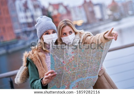 Two women wearing masks and holding map while sightseeing Gdank in Poland Royalty-Free Stock Photo #1859282116