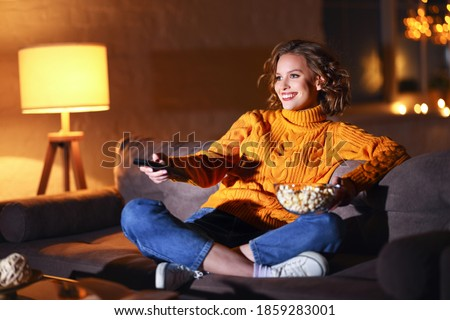 young  cheerful woman eating popcorn and watches  movie on  cable TV while switching channels with the remote control at home in evening  alone Royalty-Free Stock Photo #1859283001