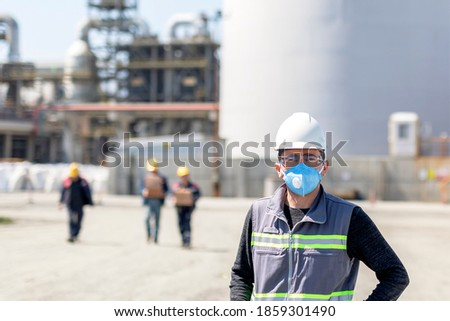 The worker is using a protective face mask for pandemic (covid-19, coronavirus) in the construction site. The group of viruses cause respiratory tract infections that can range from mild to lethal.