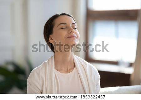 Calm leisure. Content young woman spending time at home alone, sitting on sofa with eyes closed in delight, breathing fresh cool air because of working conditioner, giving face to sunlight from window Royalty-Free Stock Photo #1859322457