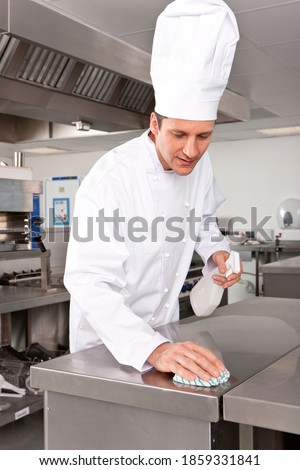 A portrait shot of a chef cleaning table surface in a kitchen.