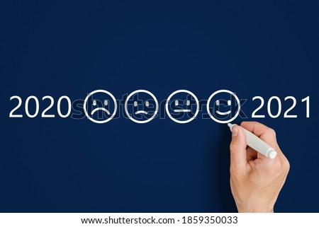 male hand draws emoticons - sad and funny next to the numbers 2020 and 2021