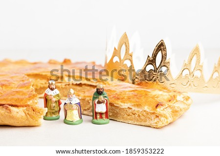 King cake or galette des rois in French. Traditional epiphany pie with golden paper crown and tiny charms Royalty-Free Stock Photo #1859353222
