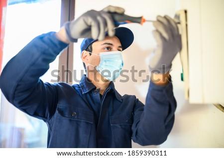 Smiling technician repairing an hot-water heater wearing a mask due to coronavirus pandemic Royalty-Free Stock Photo #1859390311