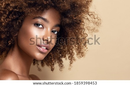 Beauty portrait of african american girl with clean healthy skin on beige background. Smiling dreamy beautiful black woman.Curly hair in afro style Royalty-Free Stock Photo #1859398453