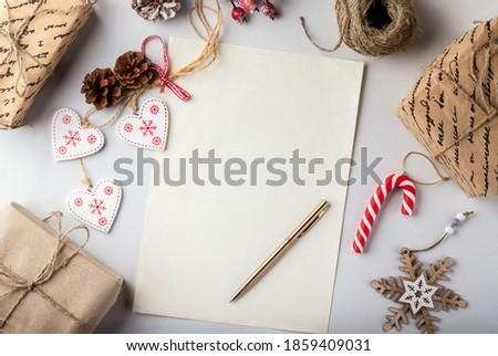 Christmas background with decorations and gift boxes , blank paper and pen on white table. Flat lay, top view.