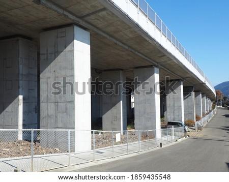 Under concrete high way and local asphalt side road against blue sky atmosphere. Highway bridge image. Concrete pile under expressway bridge. #1859435548