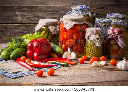 Preserved  and fresh vegetables on wooden background #185943701