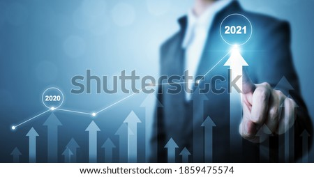 Businessman pointing arrow graph corporate future growth plan. Business development to success and growing growth year 2020 to 2021 concept Royalty-Free Stock Photo #1859475574