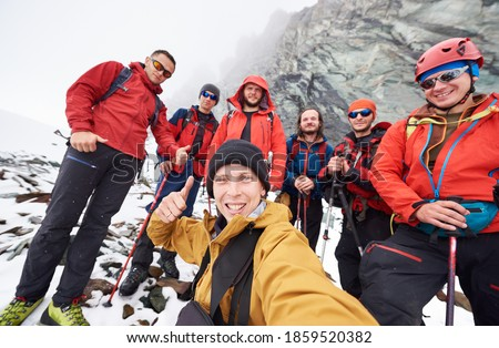 Young man taking picture with friends hikers during travel in winter mountains. Group of male travelers looking at camera and smiling, showing thumbs up. Concept of travelling, hiking and photography.