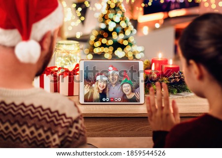 Stock photo of a young couple having a Christmas video call with their family. Concept of family in quarantine during Christmas because of the coronavirus. Xmas still life with a tablet in a cozy room #1859544526
